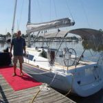 happy customer posing with sailboat