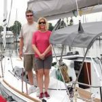 happy couple standing on sailboat