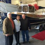 happy owners standing in front of new Ranger tug