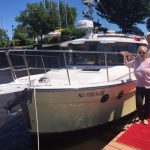 happy owners standing alongside new boat on dock