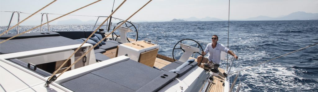 man steering oceanis 51 sailboat